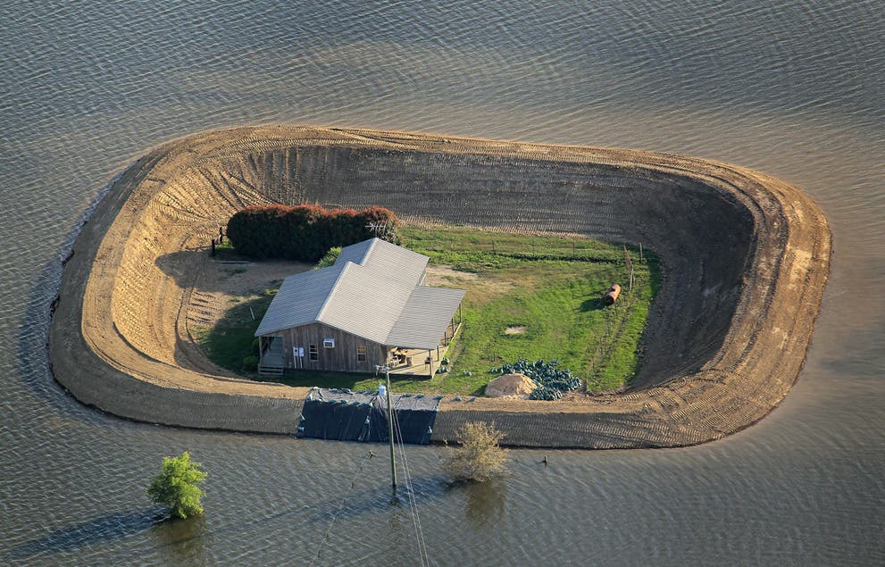 A bastion of dry land protected by a levee in the midst of the flooded Yazee. (c) Scott Olson/Getty Images