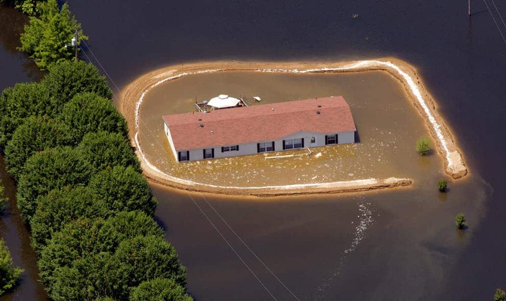 A flooded home surrounded by a makeshift levee that failed in Vicksburg, Mississippi. (c) AP Photo/Dave Martin