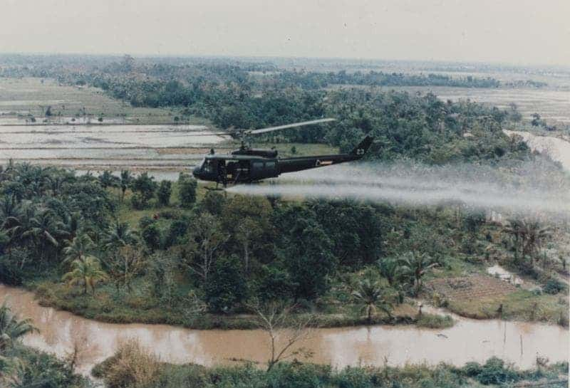 U.S. Army Huey helicopter spraying Agent Orange over Vietnamese agricultural land