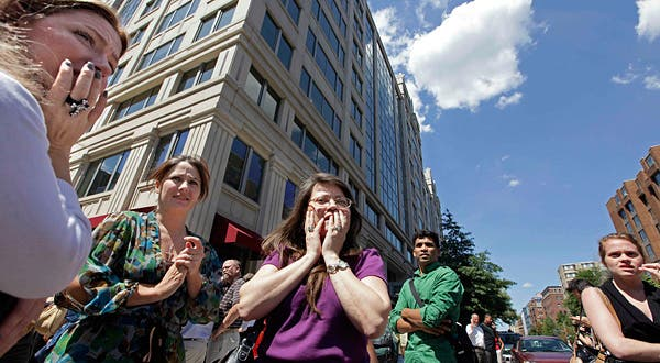 Office workers gather on the sidewalk in downtown Washington, Tuesday, moments after a 5.9 magnitude tremor shook the nation's capitol. (c) J. Scott Applewhite/Associated Press