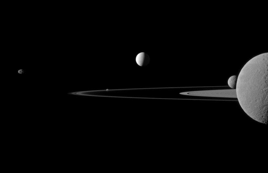 Brightly reflective Enceladus (504 kilometers, 313 miles across) appears above the center of the image. Saturn's second largest moon, Rhea (1528 kilometers, 949 miles across), is bisected by the right edge of the image. The smaller moon Mimas (396 kilometers, 246 miles across) can be seen beyond Rhea also on the right side of the image. (c) NASA
