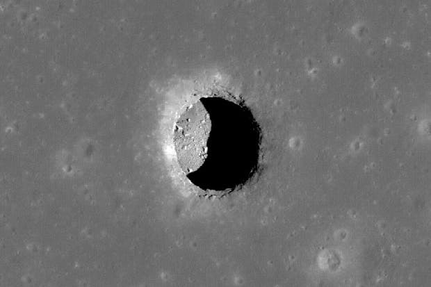 A high resolution image taken by NASA's LROC shows a 100m deep cave inside the moon's surface. (c) NASA