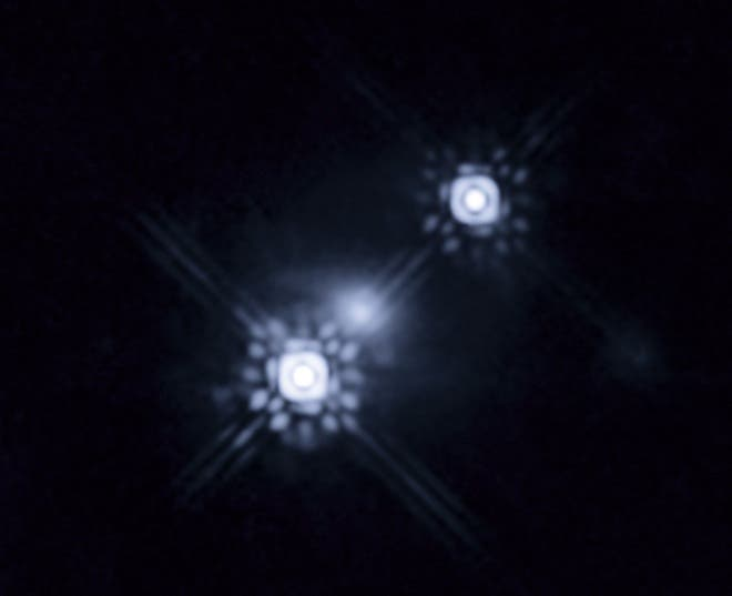 This picture shows a quasar that has been gravitationally lensed by a galaxy in the foreground, which can be seen as a faint shape around the two bright images of the quasar. Observations of one of the images show variations in colour over time. This is caused by stars within the lens galaxy passing through the path of the light from the quasar, magnifying the light from different parts of the quasar's accretion disc as they move. This has allowed a team of scientists to reconstruct the colour and temperature profile of the accretion disc with unprecedented precision. The level of detail involved is equivalent to being able to study individual grains of sand on the surface of the Moon while standing on Earth. (c) NASA