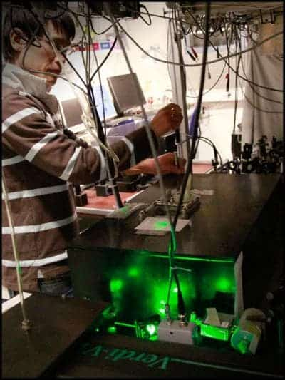 Koji Usami, one of the researchers involved in the paper, maneuvering the experiment at the Quantop laboratories at the Niels Bohr Institute. The laser light that hits the semiconducting nanomembrane is controlled with a forest of mirrors. (c) Niels Bohr Institute
