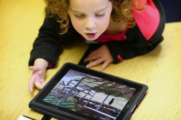 Rachel Ross, 4, a preschooler at Burley Elementary School, uses the iPad with other students in the classroom as the class looks at pictures of classrooms in Australia on Wednesday April 27, 2011.  (William DeShazer/ Chicago Tribune) B581231575Z.1 ....OUTSIDE TRIBUNE CO.- NO MAGS,  NO SALES, NO INTERNET, NO TV, NEW YORK TIMES OUT, CHICAGO OUT, NO DIGITAL MANIPULATION...