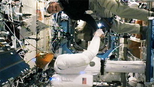 Robonaut and astronaut Daniel Burbank on Feb. 15. engaged in a firm hand shake.