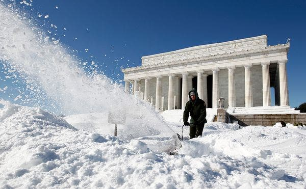 A man clearing the snow in front of the Lincoln Memorial, in Washington, DC, after a snow blizzard. (c) Reuters