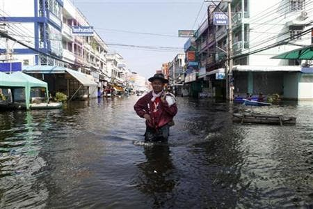 A man carrying his belongings wades through a flooded street in Nonthaburi province, on the outskirts of Bangkok November 18, 2011. (c) Reuters