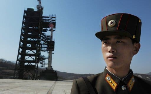 A North Korean soldier stands guard in front of the now defunct Unha-3 rocket at Tangachai -ri space center. (c) AFP
