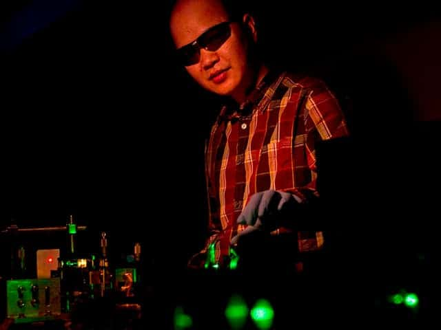 No, this is not a DJ spinning your favorite groove, although there's a laser show. The photo depicts Brown University physicist Cuong Dang directing a green laser onto a film of colloidal quantum dots, which reemit RGB light. All using a single laser.