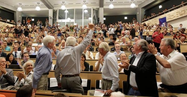 The surviving authors of the Higgs boson paper stand to a round of applause, after the discovery of the subatomic particle. (c)  Denis Balibouse