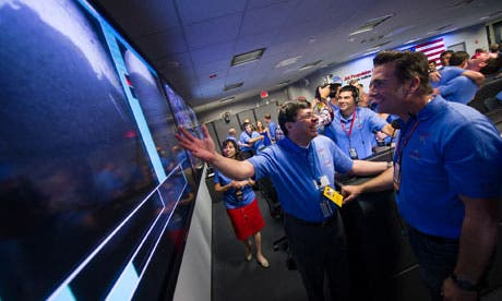 Nasa scientists look at the first images of Mars from mission control in California. (c) Reuters