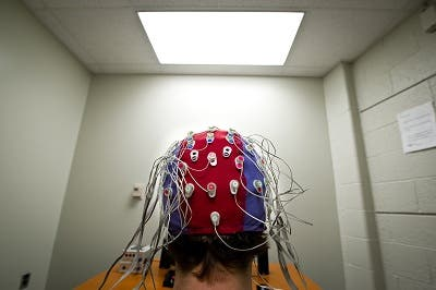 A cap worn by subjects in a Michigan State University is fitted with electrodes which pick up EEG signals at the scalp; the signals are then transmitted via optical cable to a computer where brain activity is analyzed and stored. (c) G.L. Kohuth