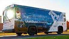 Utah State University has demonstrated a first-of-its-kind electric bus that is charged through wireless charging technology. The Aggie Bus, shown here driving through USU's Innovation Campus, achieved several significant milestones. (c) USU