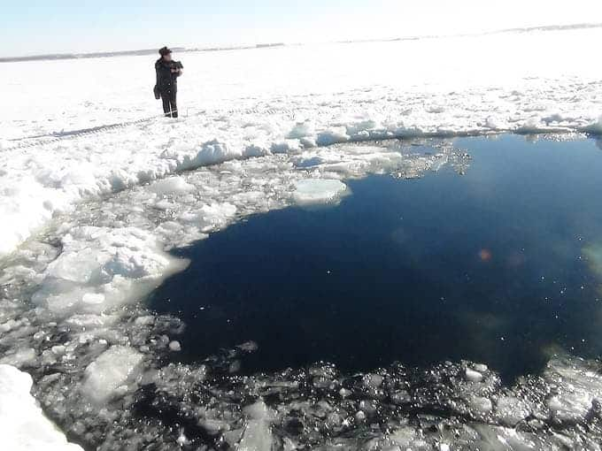 A man stands near a hole in the ice on Chebarkul Lake after a meteor strike. (c)  AP