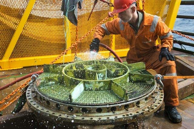 A crewman sprays water over a recovered injector plate. (c) Bezos Expeditions