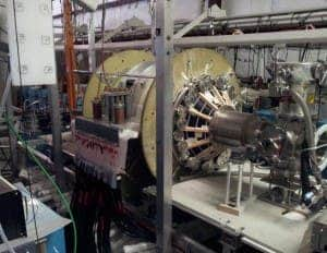 The fusion driven rocket test chamber at the UW Plasma Dynamics Lab in Redmond. The green vacuum chamber is surrounded by two large, high-strength aluminum magnets. These magnets are powered by energy-storage capacitors through the many cables connected to them. (c) University of Washington