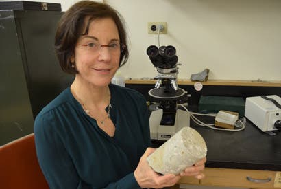 Marie Jackson holds a 2,000-year-old sample of maritime concrete from the first century B.C. Santa Liberata harbor site in Tuscany.
