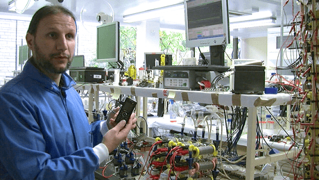 Dr Ioannis Ieropoulos inside the Bioenergy laboratory at the BRL, holding a phone powered by a microbial fuel cell stack. (c) Bristol University