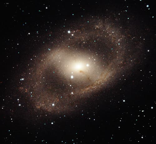 NGC 6300 is an intriguing barred spiral galaxy in the constellation of Ara. This near-infrared image with FLAMINGOS-2 shows the galaxy's complex arm structure forming a spectacular ring of star formation. The galaxy's bar also has a strong vein of dust that almost obscures its bright active nucleus –– whose prodigious energy is the result of matter accreting onto a black hole with an estimated mass of 280,000 Suns. Field of view: 3.1 x 2.9 arcmin. Credit: Gemini Observatory/AURA