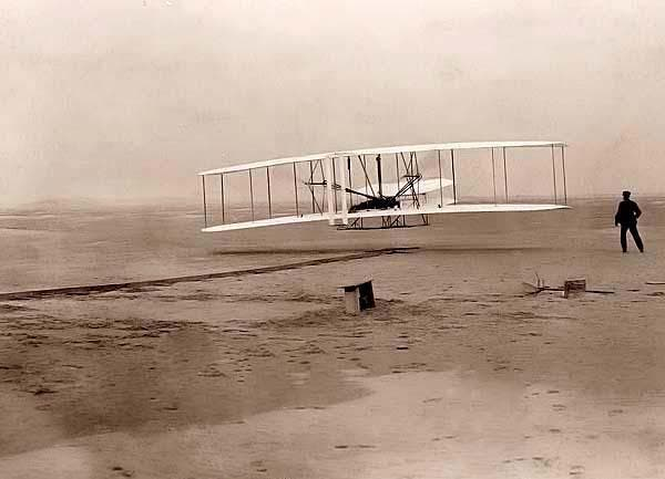 Here for your consideration is an old picture of First flight, 120 feet in 12 seconds, 10:35 a.m.; Kitty Hawk, North Carolina. It was created in 1903. Orville Wright is at the controls of the machine, lying prone on the lower wing with hips in the cradle which operated the wing-warping mechanism. Wilbur Wright running alongside to balance the machine, has just released his hold on the forward upright of the right wing. The starting rail, the wing-rest, a coil box, and other items needed for flight preparation are visible behind the machine.