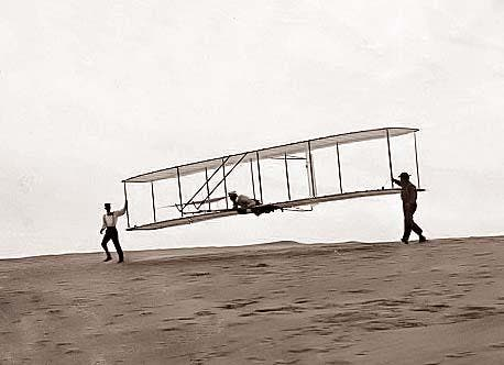 Wilbur in motion at left holding one end of glider (rebuilt with single vertical rudder), Orville lying prone in machine, and Dan Tate at right; Kitty Hawk, North Carolina. It was taken in 1902.
