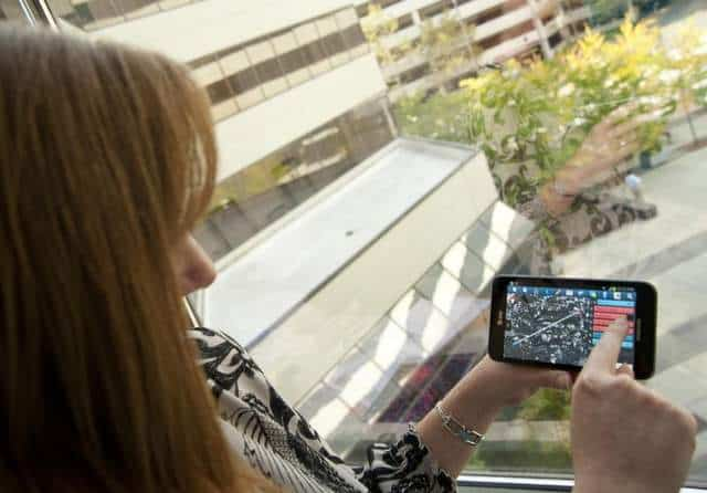 Laura Major of Draper Laboratory holds an Android device with the airstrike app open. (Draper Laboratory)