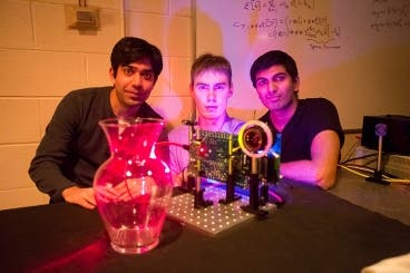 "MIT students (left to right) Ayush Bhandari, Refael Whyte and Achuta Kadambi pose next to their ""nano-camera"" that can capture translucent objects, such as a glass vase, in 3-D."