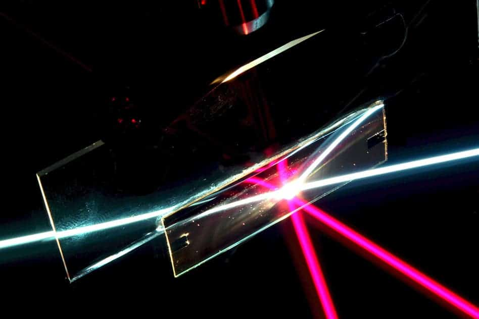 In this photo of the angular-selective sample (the rectangular region), a beam of white light passes through as if the sample was transparent glass. The red beam, coming in at a different angle, is reflected away, as if the sample was a mirror. The other lines are reflections of the beams. (This setup is immersed in liquid filled with light-scattering particles to make the rays visible). (credit: Weishun Xu and Yuhao Zhang)