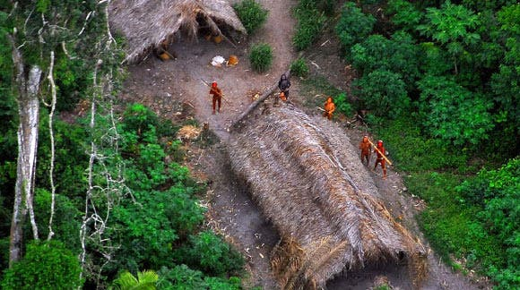 An Amazonian isolated village, with natives in the background. Some of them can be seen with their bows readied to shoot the small plane or drone used to take their picture. Photo: Government of Brazil
