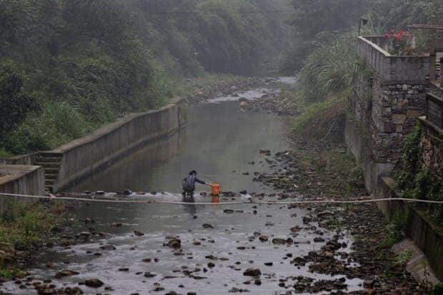 A villager washes clothes in a river. In 2010, 157 villagers from Heshan, with a population of about 1,500, had died of cancer caused by arsenic poisoning in the previous two decades, and another 190 had developed cancer due to arsenic poisoning.