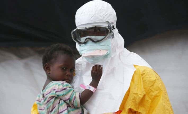A Doctors Without Borders health worker in protective clothing holds a child suspected of having Ebola in Paynesville, Liberia. Image: Getty