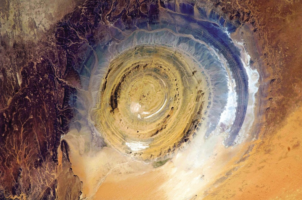 The Richat Structure in Mauritania, also known as the Eye of the Sahara, is a landmark for astronauts. If you've been busy doing experiments and haven't looked out the window for a while, it's hard to know where you are, especially if you're over a vast 3,600,000-square-mile desert. This bull's-eye orients you, instantly. Oddly, it appears not to be the scar of a meteorite but a deeply eroded dome, with a rainbow-inspired color scheme.