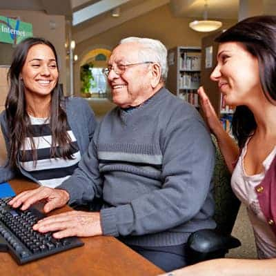 girls-teaching-old-man-how-to-use-a-computer-lg