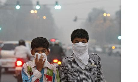 Children protect their faces from Delhi's smog. The WHO said Delhi had an average PM2.5 level of 153 – London's is a tenth of that. Photo: Hindustan Times/Getty