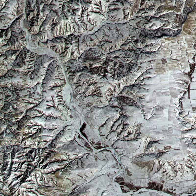 A satellite image of a section of the Great Wall of China, running diagonally from lower left to upper right (not to be confused with the much more prominent river running from upper left to lower right).
