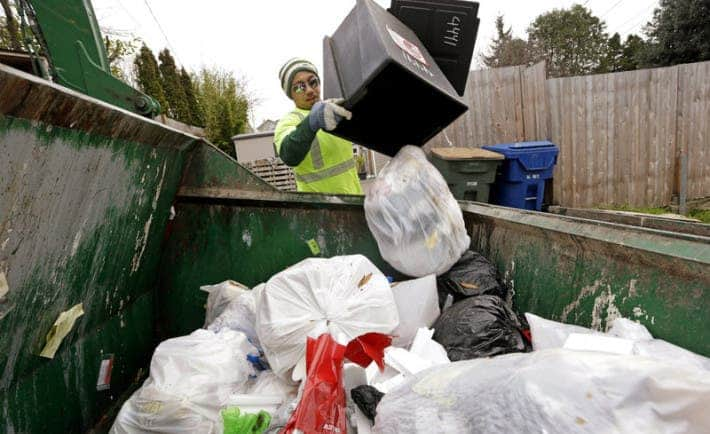 Seattle garbage collector Anousone Sadettanh empties a small residential garbage bin into his truck in 2014. It is now illegal to toss out food with the trash in the city. Residents will get warning tags for now; the city will start imposing fines in July. Elaine Thompson/AP