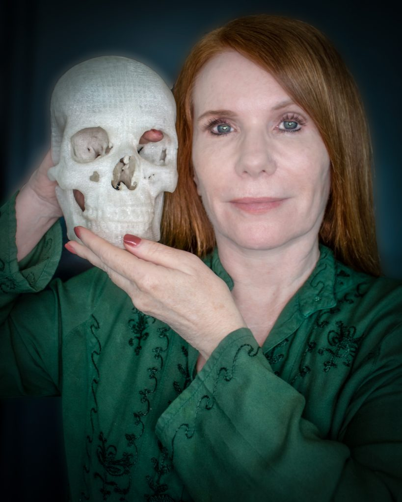 Pamela Shavaun Scott and a life-sized 3D printed version of her skull. Her tumour rests right about where her right index finger is. Image: Makezine