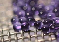 Microcapsules containing sodium carbonate solution are suspended on a mesh during carbon dioxide absorption testing. The mesh allows many capsules to be tested at one time while keeping them separated, exposing more of their surface area. Photo by John Vericella/LLNL