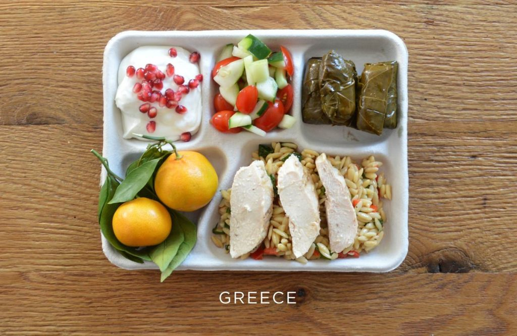 Baked chicken over orzo, stuffed grape leaves, tomato and cucumber salad, fresh oranges, and Greek yogurt with pomegranate seeds.