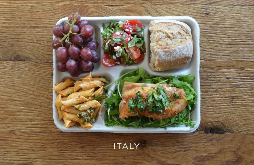 Local fish on a bed of arugula, pasta with tomato sauce, caprese salad, baguette and some grapes.