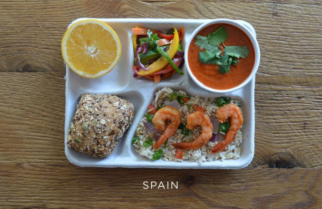 Sautéed shrimp over brown rice and vegetables, gazpacho, fresh peppers, bread and an orange.