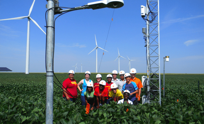 Iowa State students from the College of Engineering's Summer Program for Enhancing Engineering Development (SPEED) program pose near wind turbines and meteorological towers on an Iowa windfarm. Photo: IOWA EPSCOR