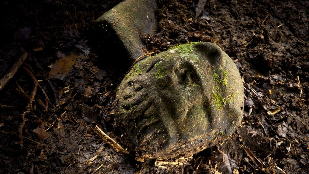 "A ""were-jaguar"" effigy, likely representing a combination of a human and spirit animal, is part of a still-buried ceremonial seat, or metate, one of many artifacts discovered in a cache in ruins deep in the Honduran jungle.  PHOTOGRAPH BY DAVE YODER, NATIONAL GEOGRAPHIC"