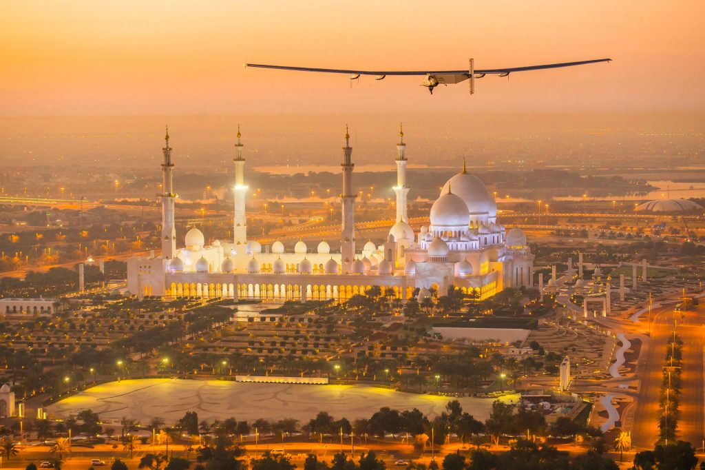 The Solar Impulse 2, a solar-powered plane, flies over the Sheikh Zayed Grand Mosque in Abu Dhabi during preparations for next month's round-the-world flight on Feb. 26, 2015
