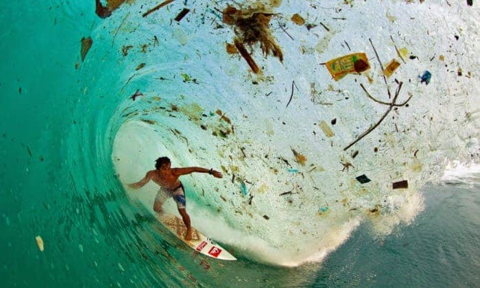Indonesian surfer Dede Surinaya catches a wave in a remote but garbage-covered bay on Java, Indonesia, the world's most populated island. Photograph: Zak Noyle