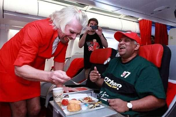 Sir Richard Branson, founder and chairman of Virgin Group, dressed as a stewardess on an AirAsia X flight after losing a bet with AirAsia's owner Tony Fernandes. If there's one thing Branson doesn't lack, it's status. Image: Robert Scoble