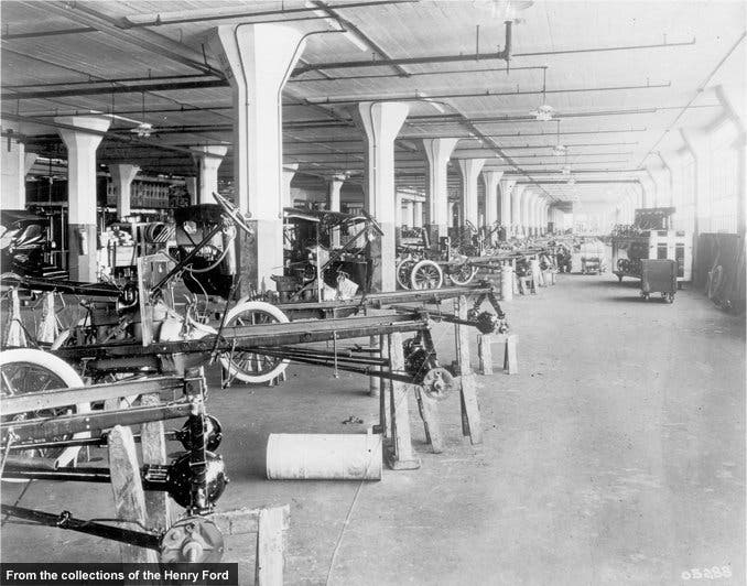 Rather than the car coming to individual workers, a team of workers came to the car. Ford, like other auto makers of the time, produced cars in this fashion for four years before the introduction of the moving assembly line.