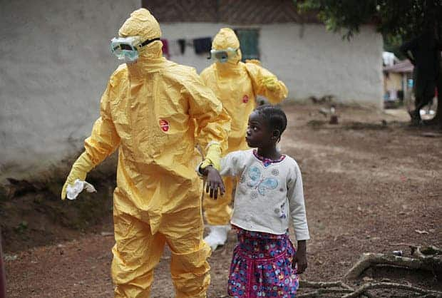 Nowa Paye, 9, is taken to an ambulance after showing signs of the ebola. Image: Telegraph