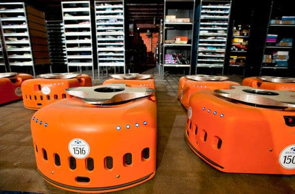 Kiva Systems' orange robots are designed to move around warehouses and stock shelves. The company was bought by Amazon in 2012 for $775 million in cash. Current robots are being designed to work alongside people, not replace them, in the work force. Image: Bloomberg